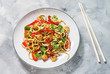 Stir fry noodles with vegetables and shrimps on concrete background
