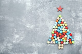 Colorful paper stars in shape of christmas tree on grey wooden table