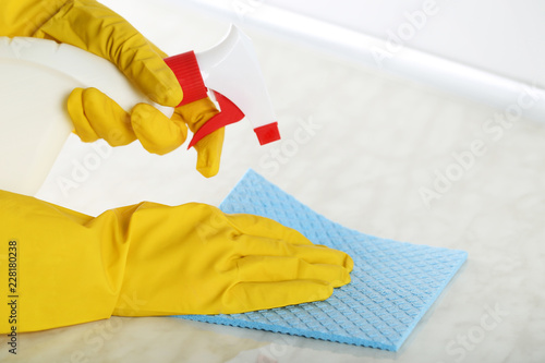 Leinwandbild Motiv Hands in gloves with sponge and bottle of detergent cleaning kitchen table