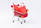 Shopping  bag full on shopping cart on white background. - 228180849