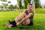 Beautiful young blond woman wearing tan pantyhose changing her heels behind a grassy knoll. - 228181674