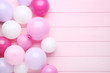 Quadro Colorful balloons on pink wooden table