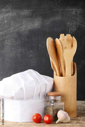 Chef hat with cooking utensils and vegetables on wooden table