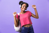 Photo of attractive african american woman wearing backpack and white headphones dancing, isolated over violet background - 228186456