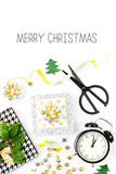 Christmas decorations with alarm clock and gifts in gold colors on white background with empty copy space for text. Holiday and celebration. Flat lay, top view
