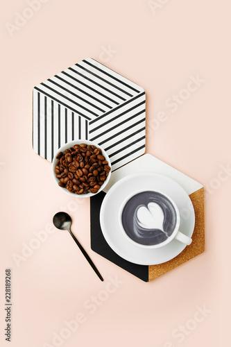Śniadanie z filiżanką kawy o geometrycznym wystroju na jasnoróżowym tle. Płaski lay, widok z góry