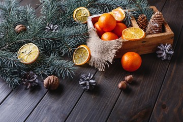 Christmas and New Year decor. Oranges, cones and Christmas tree branches lie on a wooden table