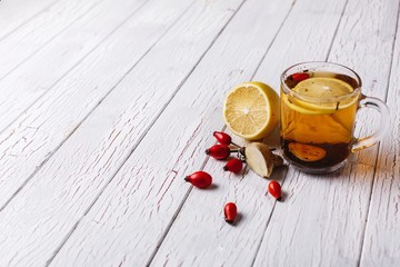 Treating cold. Hot tea with lemon and berries stands on white wooden table