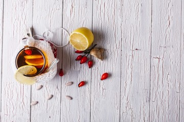Treating cold. Cup with hot tea with lemon and berries stands on a table with tables and thermometer