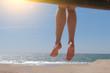 Quadro Dangling bare female feet sitting on beach.