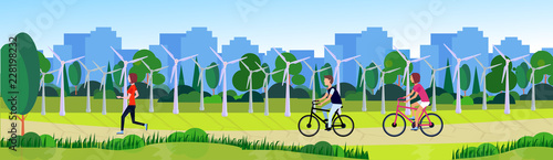 city park people running cycling clean energy wind turbines solar energy panels river green lawn trees on city buildings template background flat banner vector illustration - 228198232