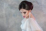 Portrait of a young elegant brunette bride with a stylish hairstyle.
