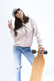 Modern Youth Concepts. Portrait of Happy Smiling Caucasian Brunette in Pink Hoodie and Warm Hat Holding Longboard In Front. Against White. - 228214885