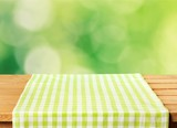 Green cloth napkin on wooden background - 228217054