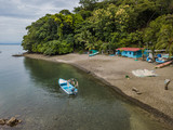 Small fishing camp on an island in the Gulf of Nicoya with fishing nets spread on the ground in Costa Rica taken by an aerial drone