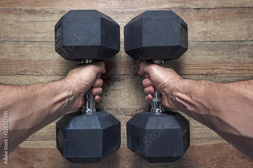 Poster black heavy dumbbells in the muscular arms of a man in the gym