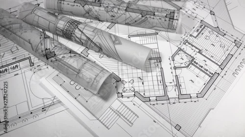 Poster Blueprints - rolls of architectural drawings smoothly rotate on the surface of the architectural plan of a modern house / seamless looping