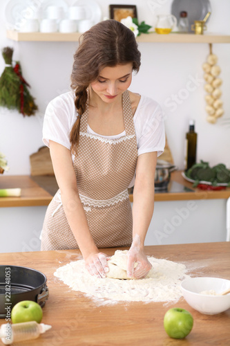Poster Young brunette woman cooking pizza or handmade pasta in the kitchen. Housewife preparing dough on wooden table. Dieting, food and health concept
