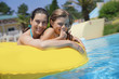 Leinwandbild Motiv Mother and daughter riding inflatable ring at the pool