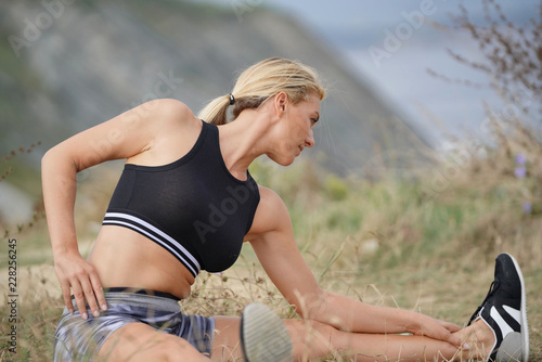 Foto Murales Woman training outside, doing stretching exercises