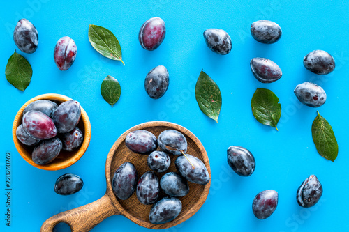 Foto Murales Blue plum for dessert. Purple plum and leaves pattern on blue background top view