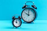 black vintage alarm clock on color background - 228260858