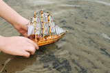 child playing with a toy sailing ship by the river, hand closeup - 228262078