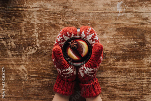 Leinwanddruck Bild cropped image of woman in mittens holding glass of mulled wine at wooden tabletop, christmas concept