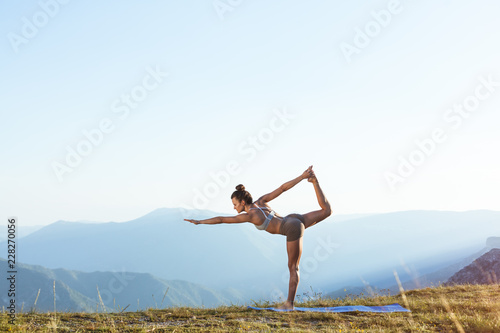 Girl balanced practicing energy yoga in the mountains.