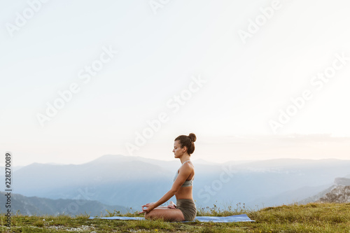 Poster Attractive girl meditating outside in a peaceful environment
