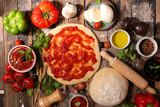 raw dough pizza with tomato sauce and ingredient
