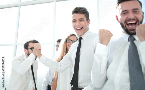 Leinwanddruck Bild happy employees standing in spacious office
