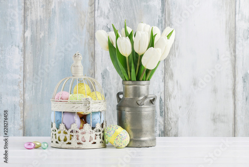 Vintage bird cage full of colorful Easter eggs and spring flowers