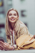 smiling blonde girl with backpack using smartphone
