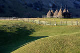 Autumn landscape in the mountains with stack of hay. Traditional hay stacks, typical rural scene of Fundatura Ponorului, Romania.  - 228286453
