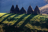 Autumn landscape in the mountains with stack of hay. Traditional hay stacks, typical rural scene of Fundatura Ponorului, Romania.  - 228286499