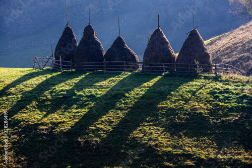 Autumn landscape in the mountains with stack of hay. Traditional hay stacks, typical rural scene of Fundatura Ponorului, Romania.