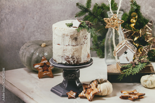 Autumn homemade white naked cake decorated by rated by star cookie and green thuja branches on cake stand fir tree, cookies, xmas decor above on white marble table. grey wall at background.