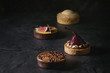 Leinwanddruck Bild - Variety of sweet tartlets with chocolate, caramel, pears, figs on black texture table.