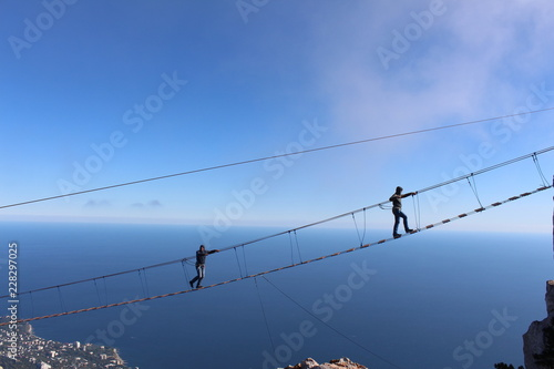 Fototapeta Father and son are on the suspension bridge at an altitude of 1234 meters