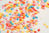 Small sweet various colourful candies on a holographic background. Minimalist pastel abstract. Top view, flat lay.