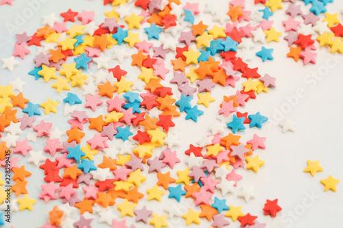 Mali słodcy różnorodni kolorowi cukierki na holograficznym tle. Minimalistyczny pastelowy abstrakcyjny. Widok z góry, płasko układany.
