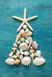 Christmas tree made from sea shells and starfish on wooden blue background, top view - 228300291