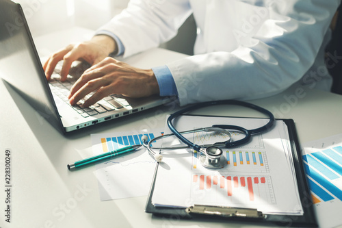 Foto Murales doctor working with medical statistics and financial reports in office
