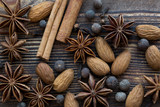 Christmas spice: cinnamon sticks, anise stars, allspice with almond nuts, macro, close-up on brown wooden rustic background, top view. - 228312883