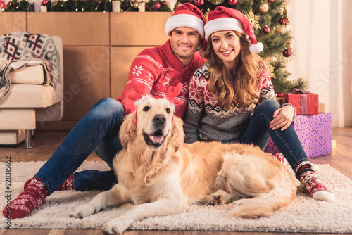 2ee5ee79c72 beautiful couple in santa hats sitting at christmas tree with retriever dog  in deer horns