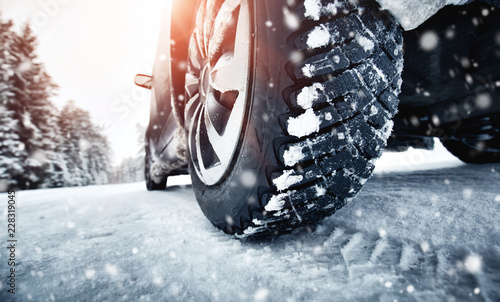 Leinwanddruck Bild Closeup of car tires in winter on the road covered with snow