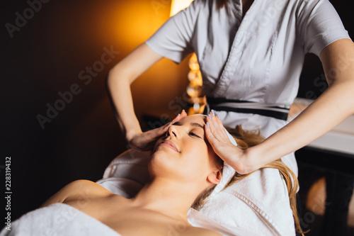 Leinwanddruck Bild Beautiful young and cute woman enjoying massage treatment