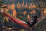 A man sits in a hammock and admires the autumn forest - 228325232