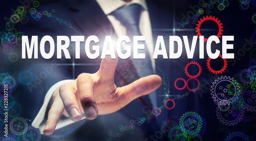 A businessman pressing a Mortgage Advice business concept on a graphical display of cogs